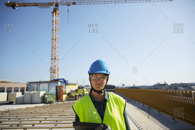 Confident female engineer in reflective clothing with digital tablet at construction site against clear sky