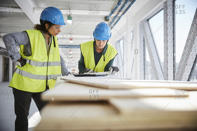 Female architects discussing over blueprint at construction site