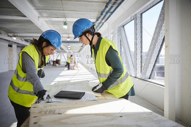 Side view of female engineers discussing over blueprint at construction site