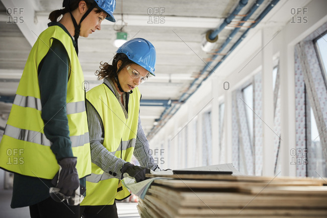 Female engineers discussing over blueprint at construction site