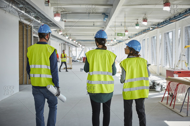 Rear view of male and female engineers walking at construction site