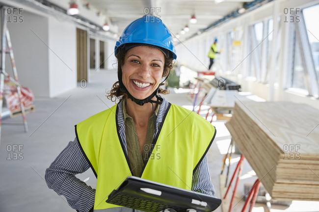 Portrait of smiling female engineer with digital tablet standing at construction site