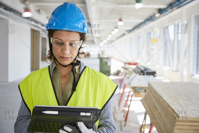 Confident female architect in reflective clothing using digital tablet at construction site