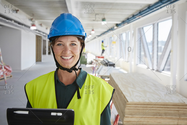Portrait of smiling female engineer in reflective clothing at construction site