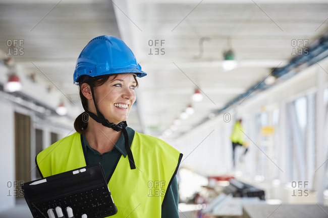 Smiling female construction manager in reflective clothing looking away