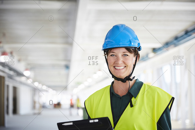 Portrait of smiling female construction manager in reflective clothing at site