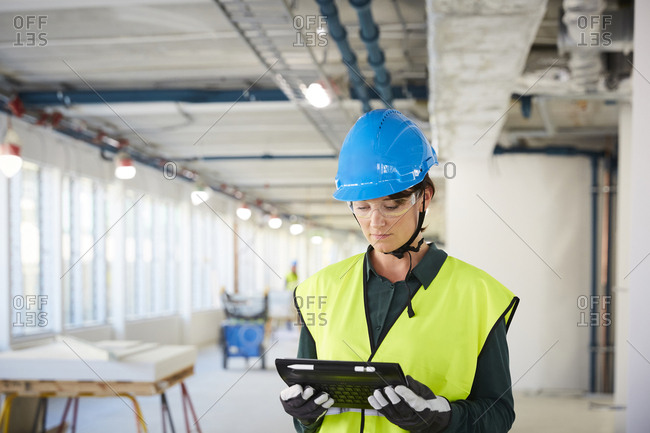 Confident female engineer in reflective clothing using digital tablet at construction site