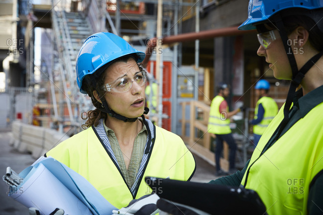 Female engineer discussing with coworker at construction site