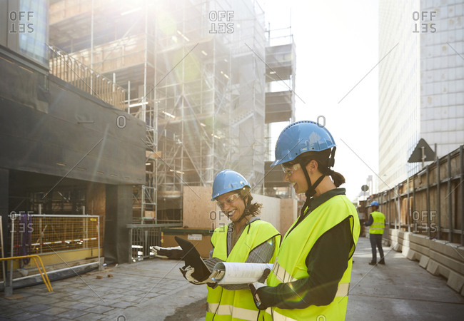 Female engineers discussing over digital tablet at construction site during sunny day