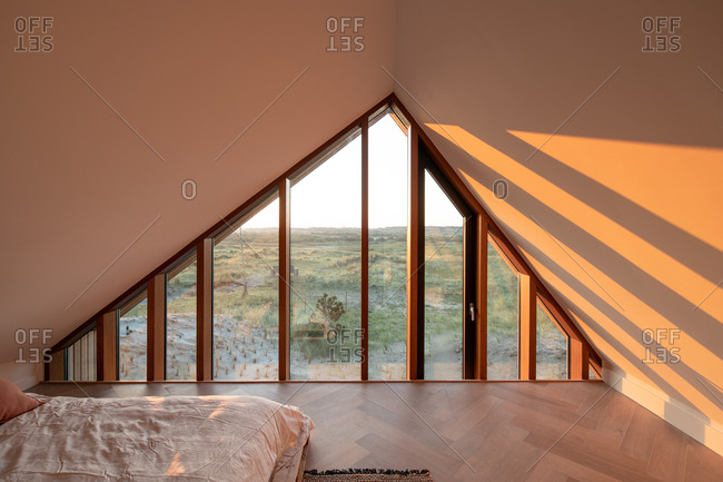Terschelling, Netherlands - September 21, 2019: The rising sun shines through a large triangular shaped window of a holiday home