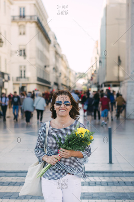 Happy woman holding yellow flowers, in busy city street