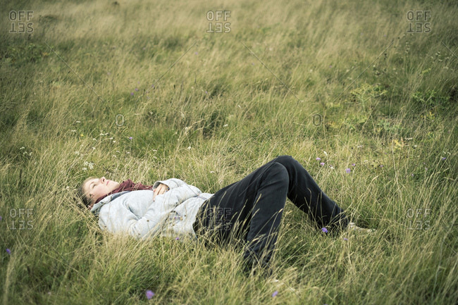 Young woman lying in the grass daydreaming.