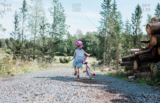 Young girl walking with her bike along a country lane in summer