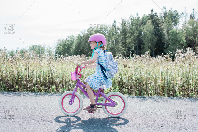 Young girl cycling along a country lane smiling in summer