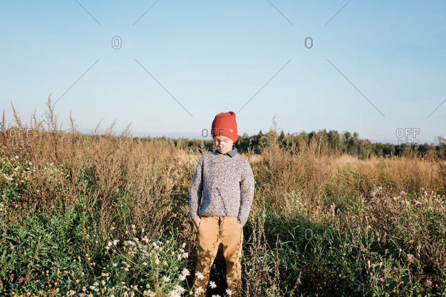 Young boy stood in a field with his hands in his pockets thinking