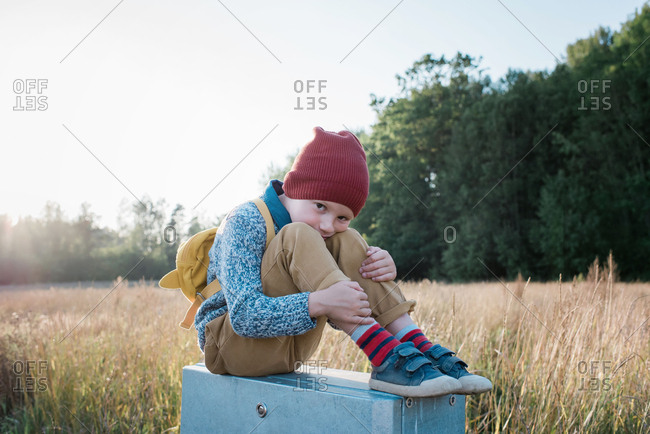 Young school boy sitting on a post whilst walking home from school