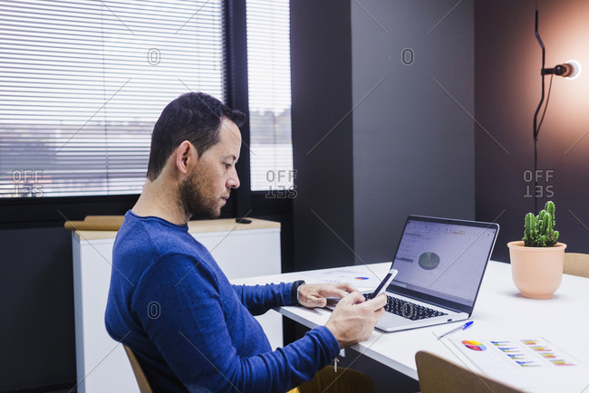 Portrait of business man reading message with smartphone in office.