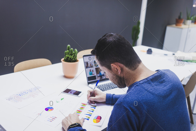 Man working on documents at desk in office