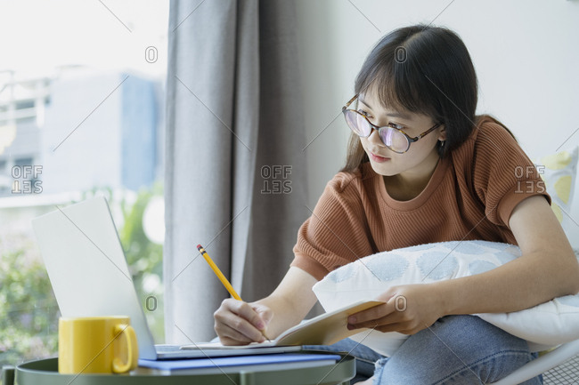 Collage student female reading and researching form book.