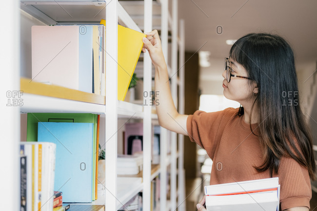 Young teenage making order on bookshelves in bookstore.