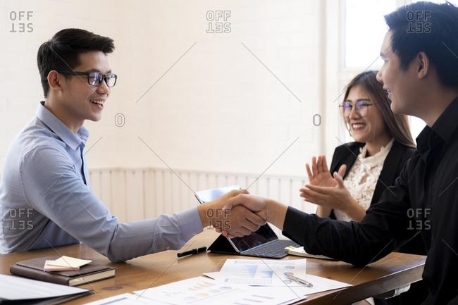 Businessmen shake hands after good deal.