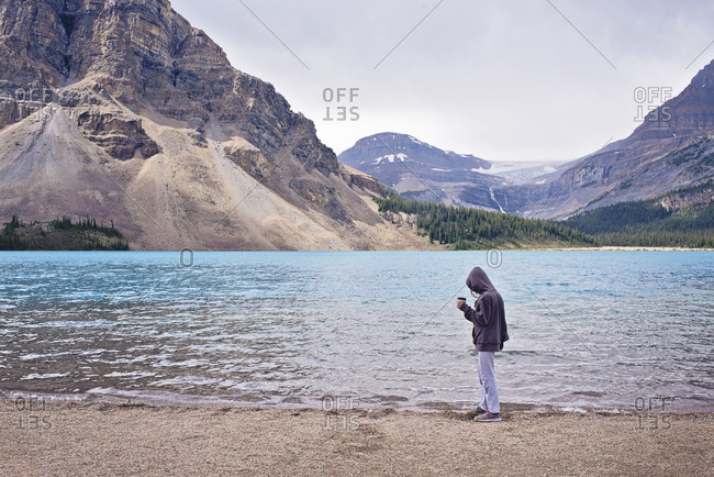 Side view of woman wearing hooded shirt holding cup while standing at lakeshore against sky