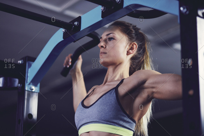 Front profile of young woman doing chin ups at fitness center