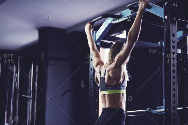 Rear profile of young woman hanging between doing chin ups at fitness center