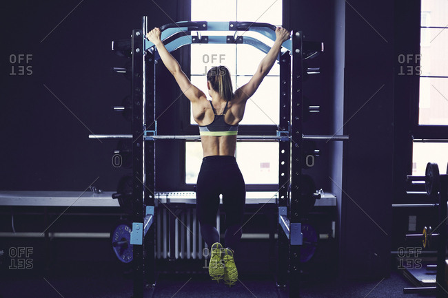 Rear profile of young woman doing chin ups at fitness center