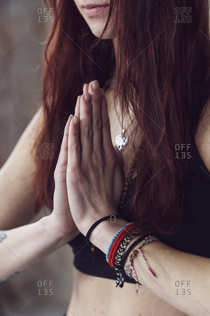 Close up of female hands in yoga pose by the brick wall