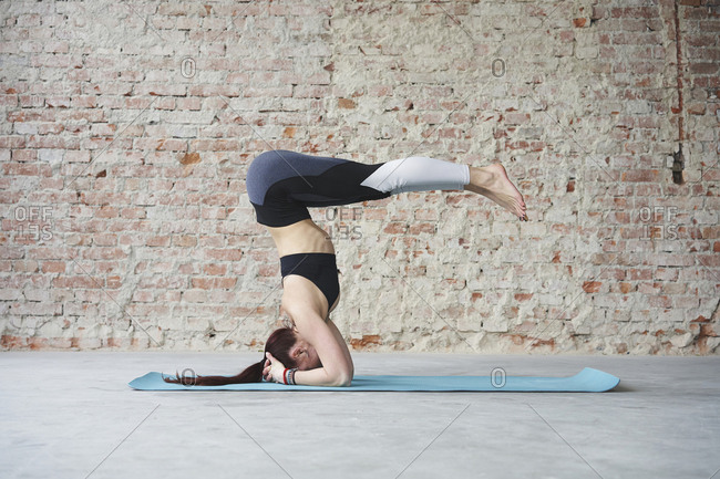 Young female in yoga pose by the brick wall