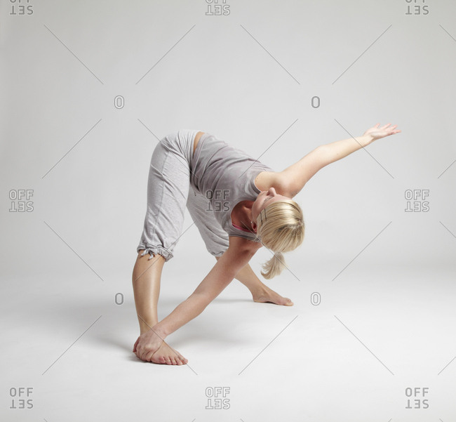 Young female doing yoga pose on clean background.