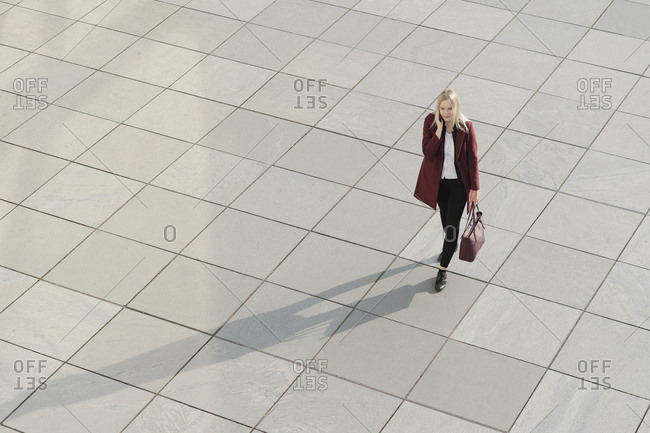 View from above of blond businesswoman using smartphone- walking on concrete ground