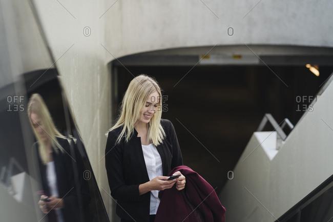 Blond businesswoman using smartphone while using escalator