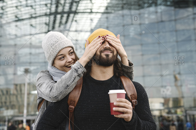 Happy young woman surprising boyfriend at the central station- Berlin- Germany