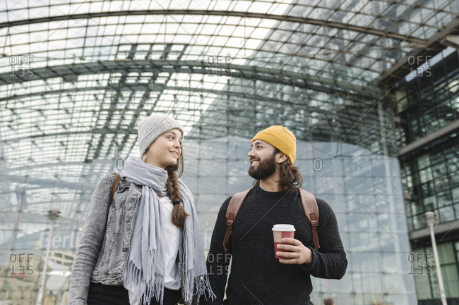 Happy young couple with takeaway coffee at the central station- Berlin- Germany