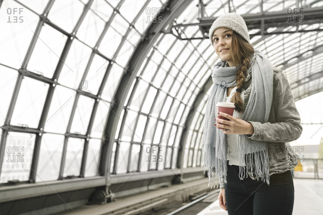 Young woman with takeaway coffee waiting at the station platform- Berlin- Germany