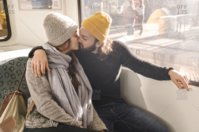 Young couple kissing on a subway