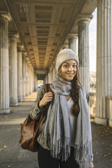 Portrait of smiling young woman in arcade in the city- Berlin- Germany