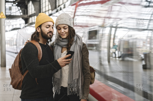 Young couple using smartphone at the station platform as the train comes in- Berlin- Germany