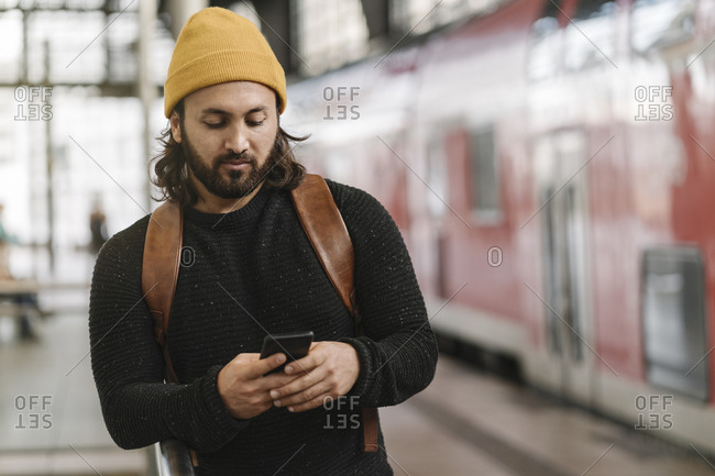 Young man using smartphone at the station platform- Berlin- Germany