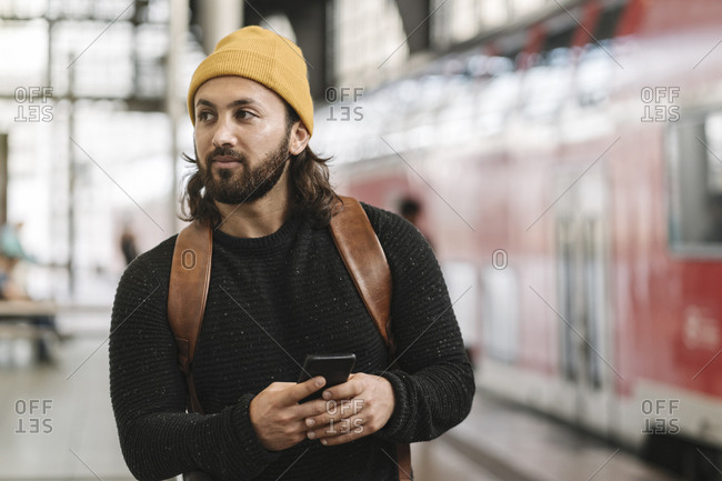 Young man with smartphone at the station platform- Berlin- Germany
