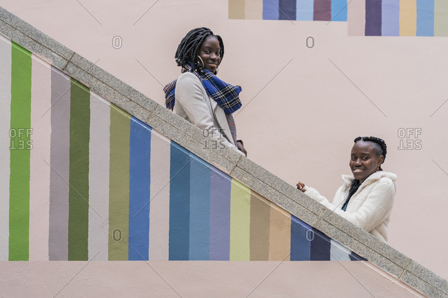 Portrait of two smiling young women  on colorful staircase
