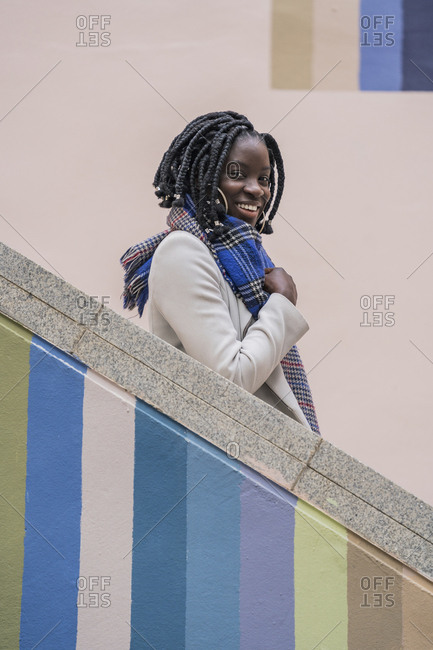 Portrait of happy young woman with black braids on colorful staircase