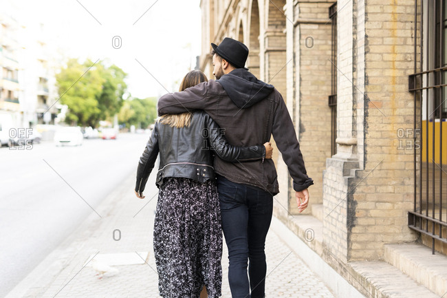 Back view of young couple in love walking arm in arm in the city