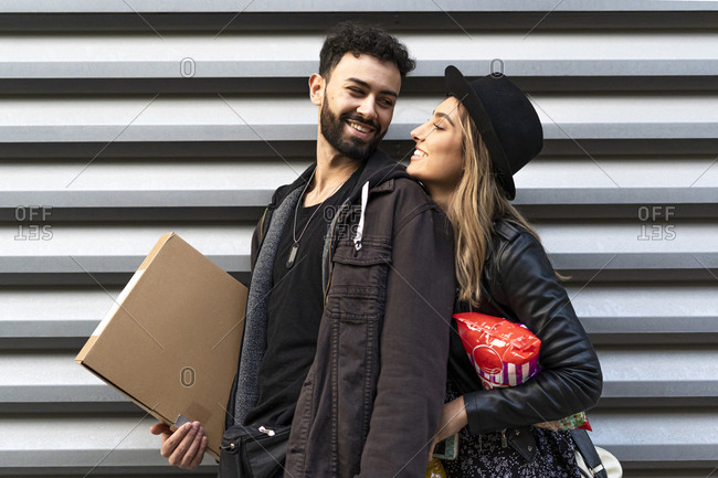 Happy young couple with purchases in the city