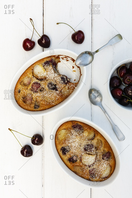 Bowls of gluten free homemade clafoutis with cherries- peaches and almonds