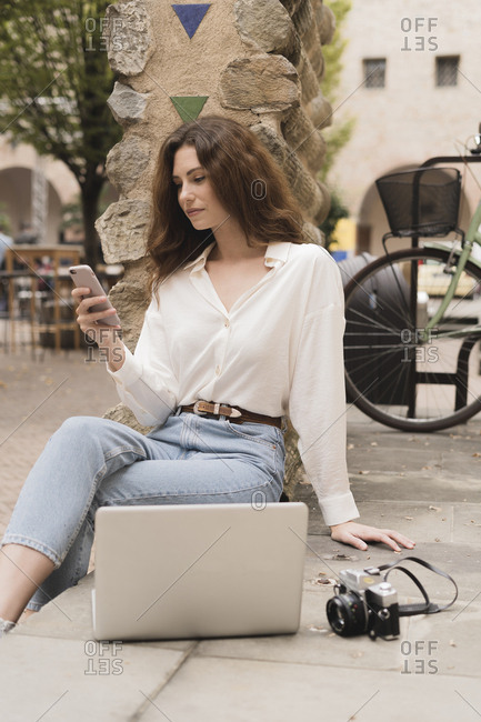 Young woman with smartphone- camera and laptop outdoors