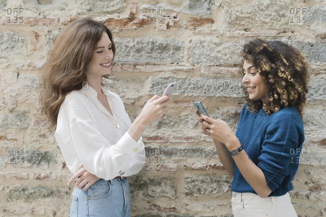 Two women using smartphones outdoors