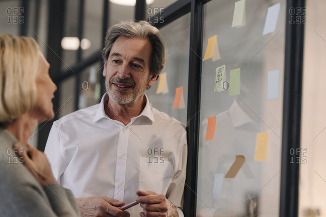 Businessman and businesswoman working on sticky notes at glass pane in office